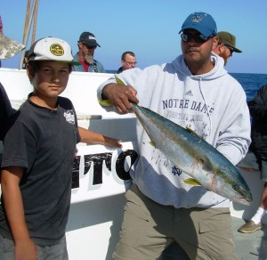 Dad with a yellowtail landed by his son
